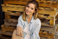 Muchacha encantadora que se sienta en una plataforma usando el teléfono elegante Foto de archivo