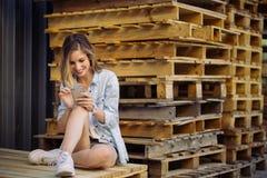 Muchacha encantadora que se sienta en una plataforma usando el teléfono elegante Fotos de archivo libres de regalías