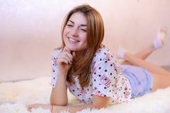 Muchacha encantadora que sonríe y que presenta, mintiendo en la alfombra en piso en b Fotografía de archivo
