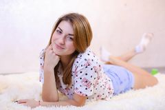 Muchacha encantadora que sonríe y que presenta, mintiendo en la alfombra en piso en b Fotografía de archivo libre de regalías