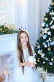 Muchacha encantadora que sonríe y que presenta en la cámara, llevando a cabo la vela en vagos Fotos de archivo libres de regalías