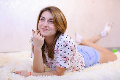 Muchacha encantadora que sonríe y que presenta, mintiendo en la alfombra en piso en b Imagen de archivo