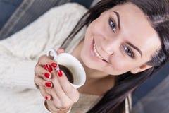 Muchacha encantadora que sostiene la taza de primer del café imagen de archivo