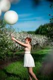 Muchacha encantadora que sostiene los globos blancos que miran tristemente ellos fotografía de archivo