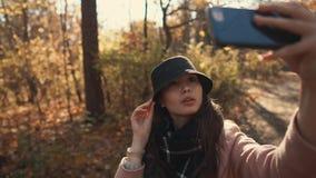 Muchacha encantadora que toma el selfie en un bosque metrajes