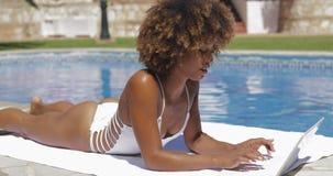 Muchacha encantadora que usa el ordenador portátil en piscina metrajes