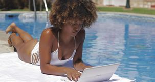 Muchacha encantadora que usa el ordenador port?til en piscina almacen de video