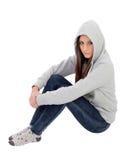 Muchacha encapuchada enojada con la camiseta gris que se sienta en el piso Fotografía de archivo