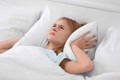 Muchacha enfadada que cubre sus oídos con la almohada Fotos de archivo libres de regalías