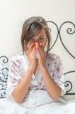 Muchacha enferma adolescente joven que se sienta en cama Foto de archivo