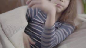 Muchacha enferma cansada que miente en cama y poner un termómetro en boca Concepto de un ni?o enfermo Medicina y salud almacen de video