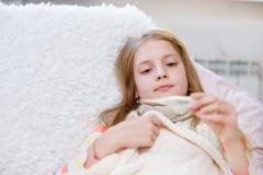 Muchacha enferma con el termómetro que miente en cama Imagenes de archivo
