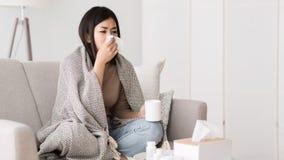 Muchacha enferma con fiebre envuelta en manta que bebe té caliente imagen de archivo
