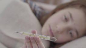Muchacha enferma del retrato que miente en cama y que muestra un termómetro en la cámara Concepto de un ni?o enfermo Medicina y s almacen de metraje de vídeo