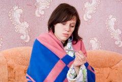 Muchacha enferma en el sofá con un termómetro Fotos de archivo
