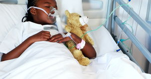 Muchacha enferma en la máscara de oxígeno que descansa con el oso de peluche almacen de metraje de vídeo