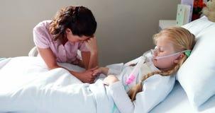 Muchacha enferma en la máscara de oxígeno que descansa sobre cama almacen de video
