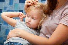 Muchacha enferma en los brazos de su madre foto de archivo