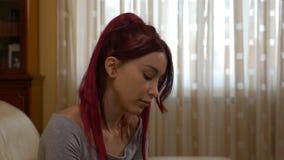 Muchacha enferma que estornuda teniendo un frío que ase su garganta dolorida y nariz que sopla en tejido metrajes