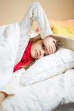 Muchacha enferma que miente en cama y que lleva a cabo la mano en la cabeza Fotos de archivo libres de regalías