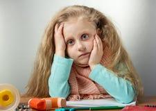 Muchacha enferma triste con la bufanda que se sienta en la tabla, al lado de medicina y del inhalador imagen de archivo