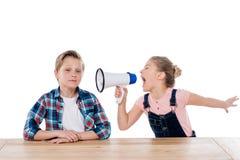 Muchacha enojada con el megáfono que grita en su hermano imagen de archivo libre de regalías