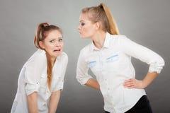 Muchacha enojada de la furia que grita en su amigo o hermana más joven imagen de archivo
