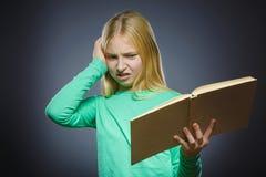 Muchacha enojada o subrayada con el libro Retrato del primer de adolescente hermoso en fondo gris concepto de los estudios Imágenes de archivo libres de regalías