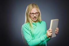 Muchacha enojada o subrayada con el libro Retrato del primer de adolescente hermoso en fondo gris concepto de los estudios Imagen de archivo