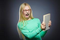 Muchacha enojada o subrayada con el libro Retrato del primer de adolescente hermoso en fondo gris concepto de los estudios Imagen de archivo libre de regalías
