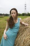 Muchacha enojada que coloca el haystack cercano Imagen de archivo
