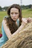 Muchacha enojada que coloca el haystack cercano Foto de archivo
