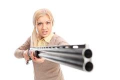 Muchacha enojada que señala un rifle en la cámara Imágenes de archivo libres de regalías