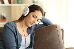 Muchacha enojada y triste que escucha la música en casa Fotografía de archivo
