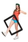 Muchacha enrrollada adolescente que se coloca con un marco Foto de archivo libre de regalías