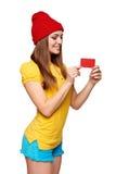 Muchacha enrrollada adolescente sonriente que sostiene la tarjeta del crédito en blanco Fotos de archivo