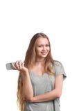 Muchacha enrrollada en una camiseta gris que presenta con un teléfono móvil Una chica joven con un pelo rubio fuerte, aislado en  Fotografía de archivo