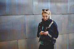 Muchacha enrrollada joven que lee agradable el texto en el teléfono de célula Fotos de archivo libres de regalías