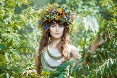 Muchacha entre árboles de las hojas con una guirnalda en su cabeza imagen de archivo libre de regalías