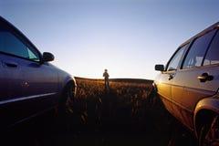 Muchacha entre dos coches Fotos de archivo