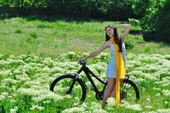 Muchacha entre las flores salvajes en una bici Imágenes de archivo libres de regalías