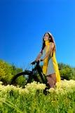 Muchacha entre las flores salvajes en una bici Imagen de archivo libre de regalías