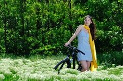 Muchacha entre las flores salvajes en una bici Foto de archivo