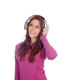 Muchacha entretenida con los auriculares que escucha la música Imágenes de archivo libres de regalías