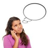 Muchacha envejecida adolescente hispánica que frunce el ceño en el teléfono Foto de archivo libre de regalías