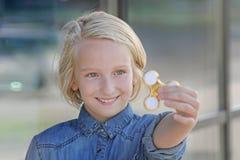Muchacha envejecida escuela linda alegre que juega con un hilandero de la persona agitada del oro Un juguete de moda popular Fotos de archivo libres de regalías