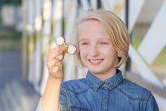 Muchacha envejecida escuela linda alegre que juega con un hilandero de la persona agitada del oro Un juguete de moda popular Fotografía de archivo libre de regalías