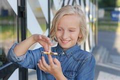 Muchacha envejecida escuela linda alegre que juega con un hilandero de la persona agitada del oro Un juguete de moda popular Imagenes de archivo