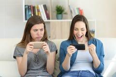 Muchacha envidiosa del perdedor que mira a su amigo del ganador fotos de archivo