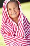 Muchacha envuelta en la toalla que se sienta en jardín Fotografía de archivo